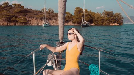 Brunette girl in one piece swimsuit posing on the bow of a sailing yacht, summer vacation at sea