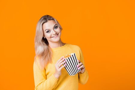 Young cheerful woman in a yellow sweater watching a movie and eating popcorn. Fan of the movie, copy space