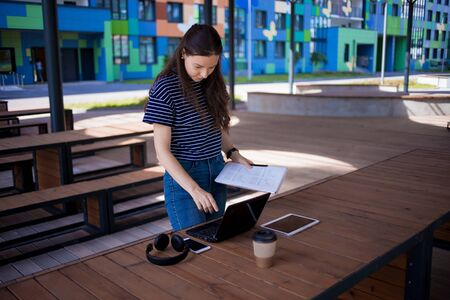 A serious, attractive brunette girl is standing in front of a wooden table with a laptop, intently studying the documents and papers she holds in her hands. On the table is a notebook,