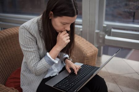 Stress at work, deadline and lack of time. Business problems. A young woman in business clothes sitting with a laptop and working in a modern office