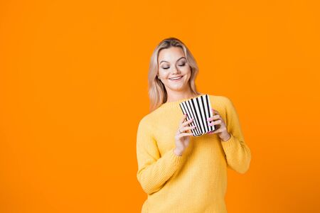 Young woman watching a movie and eating popcorn. Fun girl in yellow fan of the movie