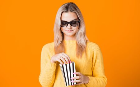 Young cheerful woman in 3D glasses watching a movie and eating popcorn. Fan of the movie, copy space