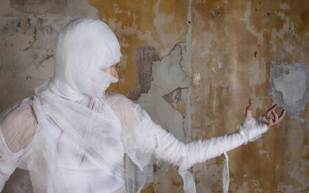 Halloween image, mummy in bandages, risen dead legendary character. young woman in the form of a mummy wrapped in bandages, against the textured old wall Stok Fotoğraf