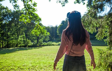 Virtual forest. A young woman in virtual reality glasses stands under the trees in a clearing, on a sunny summer day and touches the air with her hands. The view from the back. Copyspace. Фото со стока