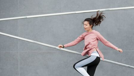 An athletic young woman is jumping, raising her knees high, running, dancing, doing acrobatics, ballet, is actively involved in sports, against a concrete wall. Copyspace.