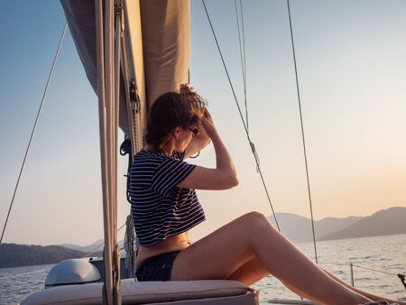 attractive young woman in a striped t-shirt enjoys the sunset on the deck of a sailing yacht. Sailing regatta, luxury vacation at sea