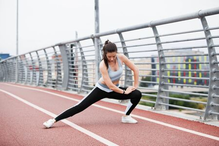 City fitness. A young sports woman in a fitness suit is warming up, doing stretching against the background of the steel railing of the bridge, the cityscape and the white sky. Copyspace.