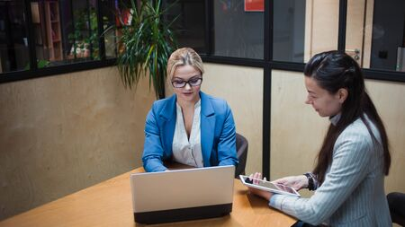 young HR woman interviews a candidate for a job. Business meeting two young women at work discussing the project. Two women in the office at the table, looking at gadgets and discussing something