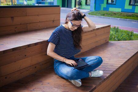 Serious brunette student girl in glasses, with an open laptop in her lap, carefully, thoughtfully looking at the monitor, straightens her hair, learns online. Outdoor. View from above