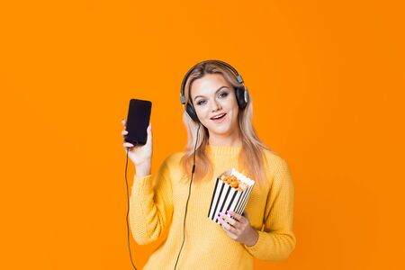 Cinema by subscription, concept. A young woman in a yellow sweater with headphones with a smartphone and popcorn in her hand. Watching movies and TV series on the streaming service. 스톡 콘텐츠