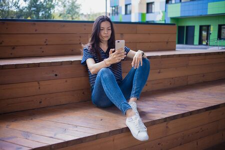 A brunette girl, a student with long hair, with a large wrist watch, in jeans, sits on wooden steps with legs and thoughtfully checks a smartphone. Front view. Outdoor. 스톡 콘텐츠