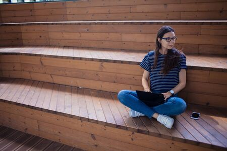 serious brunette student girl in glasses, with flowing long hair, sits crosslegged, on wooden steps, on bench, with an open laptop in her lap, typing on a keyboard, learns online. Outdoor. side view. Фото со стока