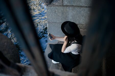 young woman in a hat and with a backpack walks in the city and uses a smartphone. Hipster on a walk uses the phone and takes photos for social networks Фото со стока