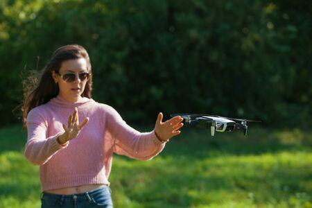 Walk with a drone. A young woman in black glasses launches a low flying drone. Reaches out to a low flying drone, gesture control. Blurred background. Front view.