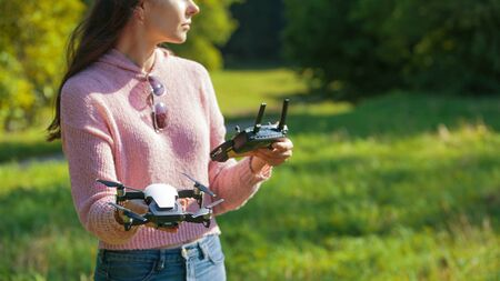 A young woman in a clearing in a park launches, checks, holds a drone, in one hand, in the other control panel. Outdor. Copyspace. Drone close up. The woman is partially visible. Imagens