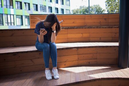 A young girl, a student, with a phone in her hand, is crying, covering her face with her hands, on a wooden bench, the stairs in the campus, on a blurred background.