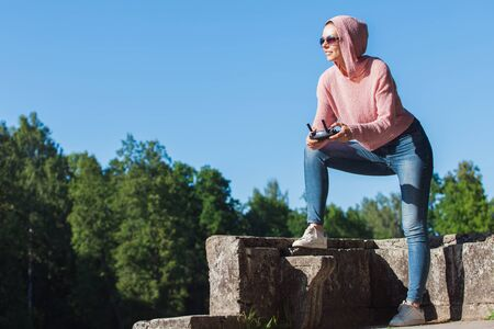 Young woman wearing sunglasses and hoodie holding a remote control, controls, controls are not visible in the frame drone. A woman carefully looks into the distance against a blue sky. Copyspace. Imagens