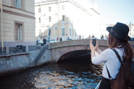 Tourist in the city takes a photo on your smartphone. Young woman in black hat and white shirt. Funny hipster girl takes selfie on phone