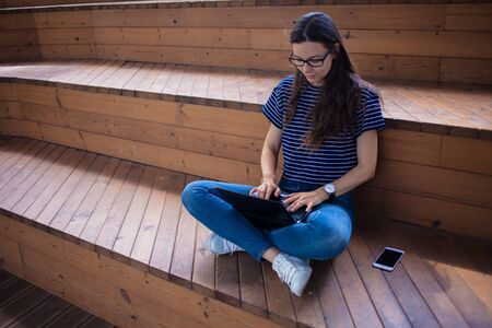 A serious brunette student girl in glasses, sits crosslegged, on wooden steps, on a bench, with an open laptop, typing on a keyboard, straightens her hair, learns online. Outdoor. Front and side view. Stockfoto