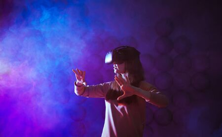Amazed young woman touching the air during the VR experience against neon and smoke futuristic background. Horizontal studio shot. Copyspace. Stockfoto