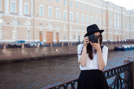 Funny hipster girl taking pictures in the city. A young woman with a hat and a camera. Tourist takes a photo of the city