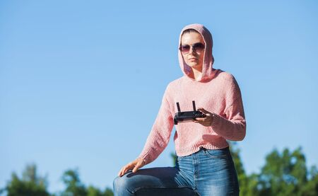 Young woman wearing sunglasses and hoodie holding a remote control, controls, controls are not visible in the frame drone. A woman carefully looks into the distance against a blue sky. Copyspace. Stockfoto
