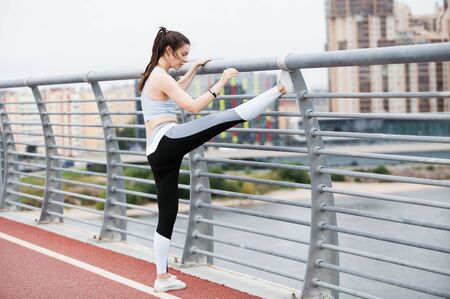 A young sports woman in a fitness suit is warming up, doing stretching at the railing of the bridge, against the backdrop of an urban cityscape.