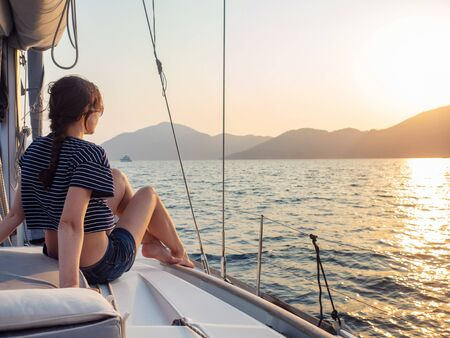 attractive young woman in a striped t-shirt enjoys the sunset on the deck of a sailing yacht. Sailing regatta, sea voyage
