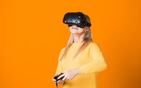 Computer game player uses virtual reality. A young woman in a virtual reality helmet with a gamepad in her hand, playing an active computer game