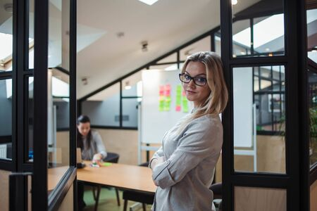 Business blonde in casual clothes in the office. Portrait of a young woman employee of the company