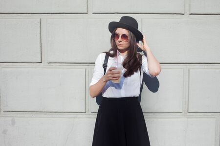 Young woman in hat and round sunglasses walking in city. Girl tourist enjoys the walk. Hipster in a hat with a backpack, Drinking coffee smoothies. On wall background, copy space