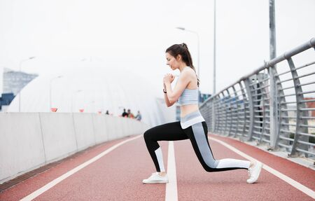 A young sports woman in a fitness suit crouches, lunges, plays sports against the backdrop of an urban cityscape and white sky. Copyspace. Stockfoto