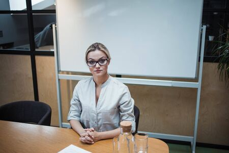 head of the meeting. A young business woman in glasses sits at a table against the background of a magnetic presentation Board