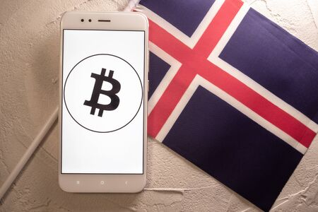 Cryptocurrency and government regulation, concept. Modern economy, smartphone with bitcoin sign on the screen on the background of the flag of Iceland