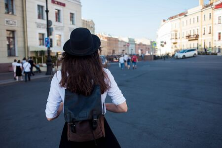 Young woman in hat walking in city, back view. Girl tourist enjoys the walk. Hipster in a hat with a backpack Stockfoto