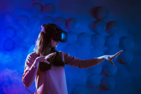 Ready for the game. The young woman in anticipation puts on virtual reality glasses, gets ready for the game, touches the air against a dark futuristic background. Copyspace.