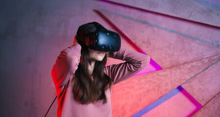 Portrait of a girl, a woman in virtual reality glasses with long dark hair, against the background of a concrete wall, backlit by neon. Side view.