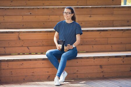 A nice young girl is sitting on wooden steps, holding a cup of coffee and a closed laptop in hand, finished work, takes a break, looks at the frame, smiles. Outdoor.