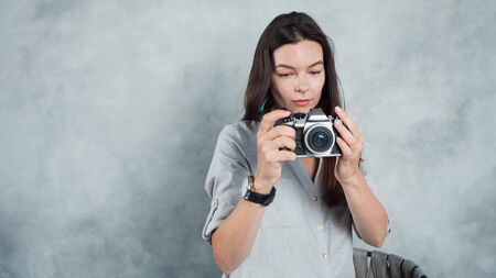 photographer takes the photo. Young successful woman contributor for photo banks. Girl with a modern camera in hand, the photographer on a gray background Stockfoto