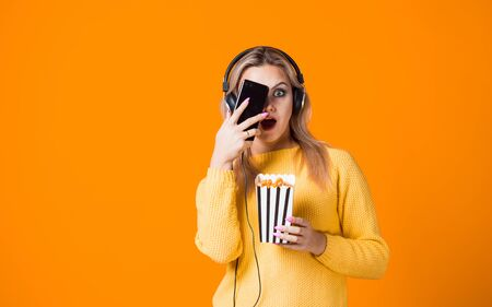 Cinema by subscription, concept. A young woman in a yellow sweater with headphones with a smartphone and popcorn in her hand. Watching movies and TV series on the streaming service. 版權商用圖片