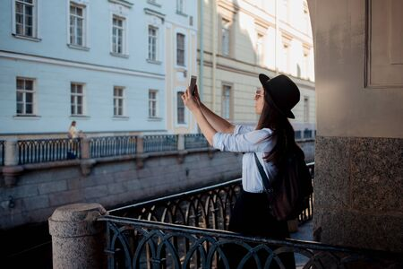 Tourist in the city takes a photo on smartphone. A young woman in a black hat and a white shirt, happy travels Stockfoto