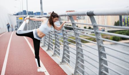 Eine junge Sportlerin im Fitnessanzug wärmt sich auf und streckt sich am Brückengeländer vor dem Hintergrund eines urbanen Stadtbildes. Exemplar.