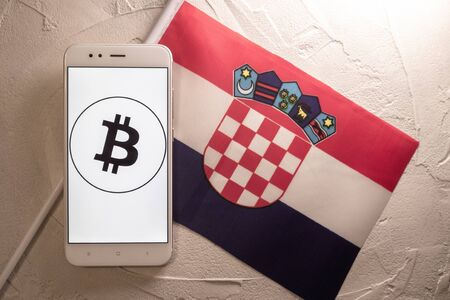 Cryptocurrency and government regulation, concept. Modern economy, smartphone with bitcoin sign on the screen on the background of the flag of Croatia
