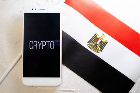 Cryptocurrency and government regulation, concept. Modern economy, smartphone with bitcoin sign on the screen on the background of the flag of Egypt