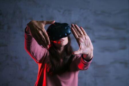 Reboot A young woman in virtual glasses spreads her arms in a characteristic gesture. Setting up a system, uses a virtual control panel, search, against a dark concrete wall.