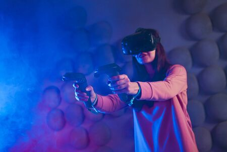 First-person shooter. A woman with glasses and a virtual reality helmet uses game controllers in both hands, like guns. Copyspace.