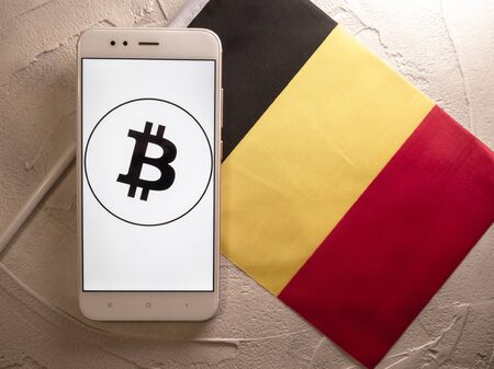 Cryptocurrency and government regulation, concept. Modern economy, smartphone with bitcoin sign on the screen on the background of the flag of Belgium
