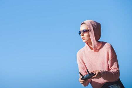 Young woman wearing sunglasses and hoodie holding a remote control, controls, controls are not visible in the frame drone. A woman carefully looks into the distance against a blue sky. Copyspace. 版權商用圖片