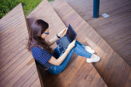 A serious brunette student girl in glasses with loose long hairs sits with legs on wooden steps, a bench, with an open laptop on her lap. Studying online. Outdoor. Top and side view.