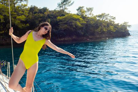attractive young woman in a bright yellow one-piece swimsuit on Board a white sailing yacht. Mooring near the island, rest on the sea.